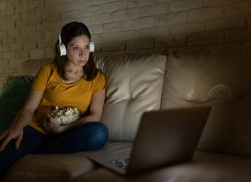 A woman in her 40s wearing headphones and eating popcorn while watching a movie on a streaming service on a laptop at night.