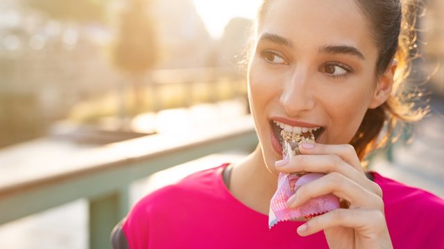 young woman eating protein bar during run