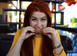 A woman biting from crispy meat and being hungry,shot taken inside fast food restaurant, looking at camera with raised eyebrow.