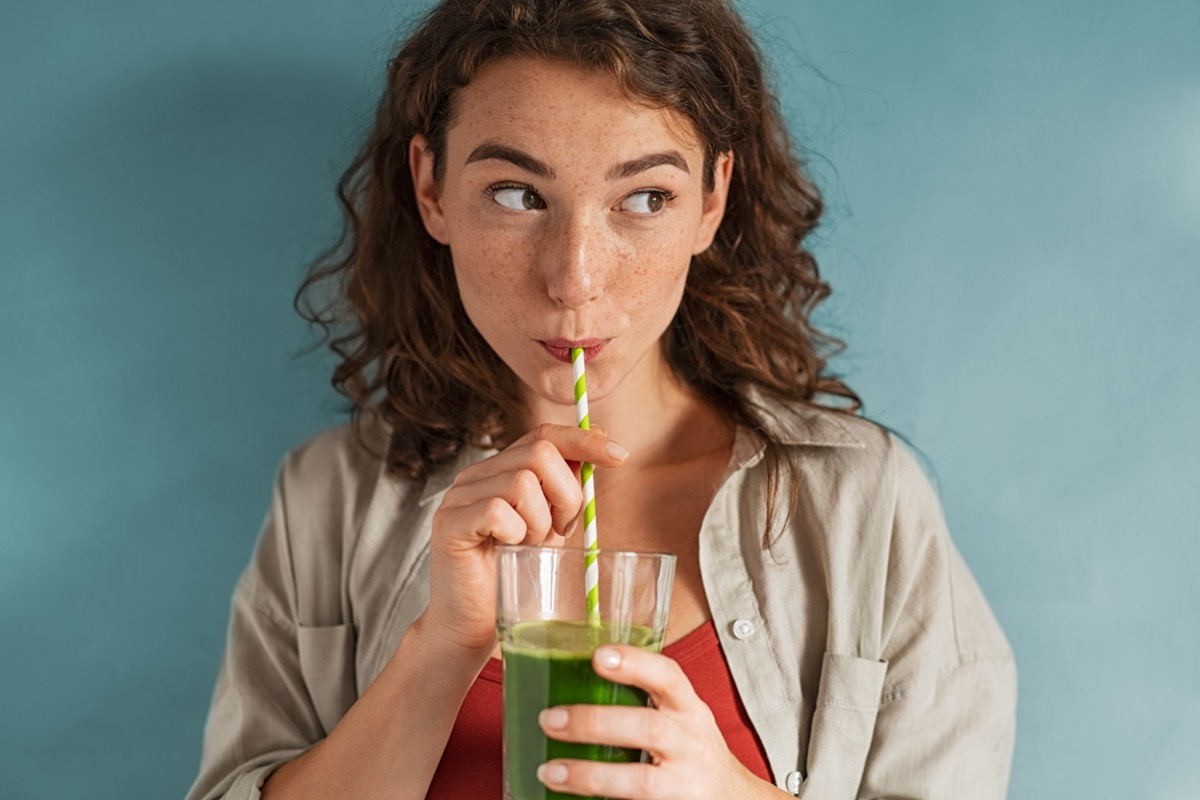 woman drinking an organic green smoothie