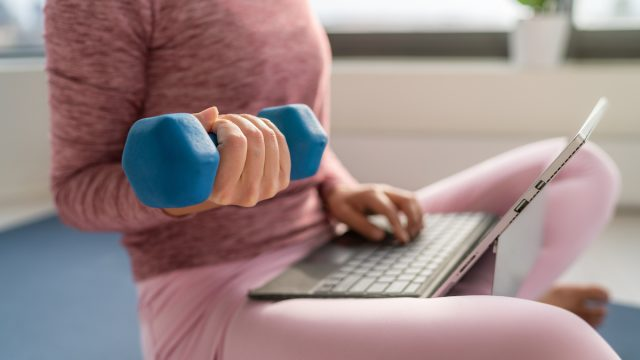 Fitness workout and working on laptop computer - woman multitasking remote work at home indoors lifting dumbbell weights for strength training while inside.