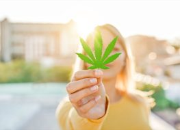 Young girl holding marijuana leaf with sunlight.