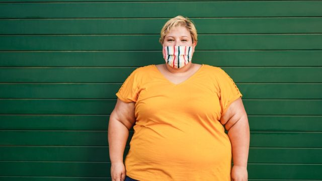 Happy plus size woman wearing a face protective mask during coronavirus outbreak