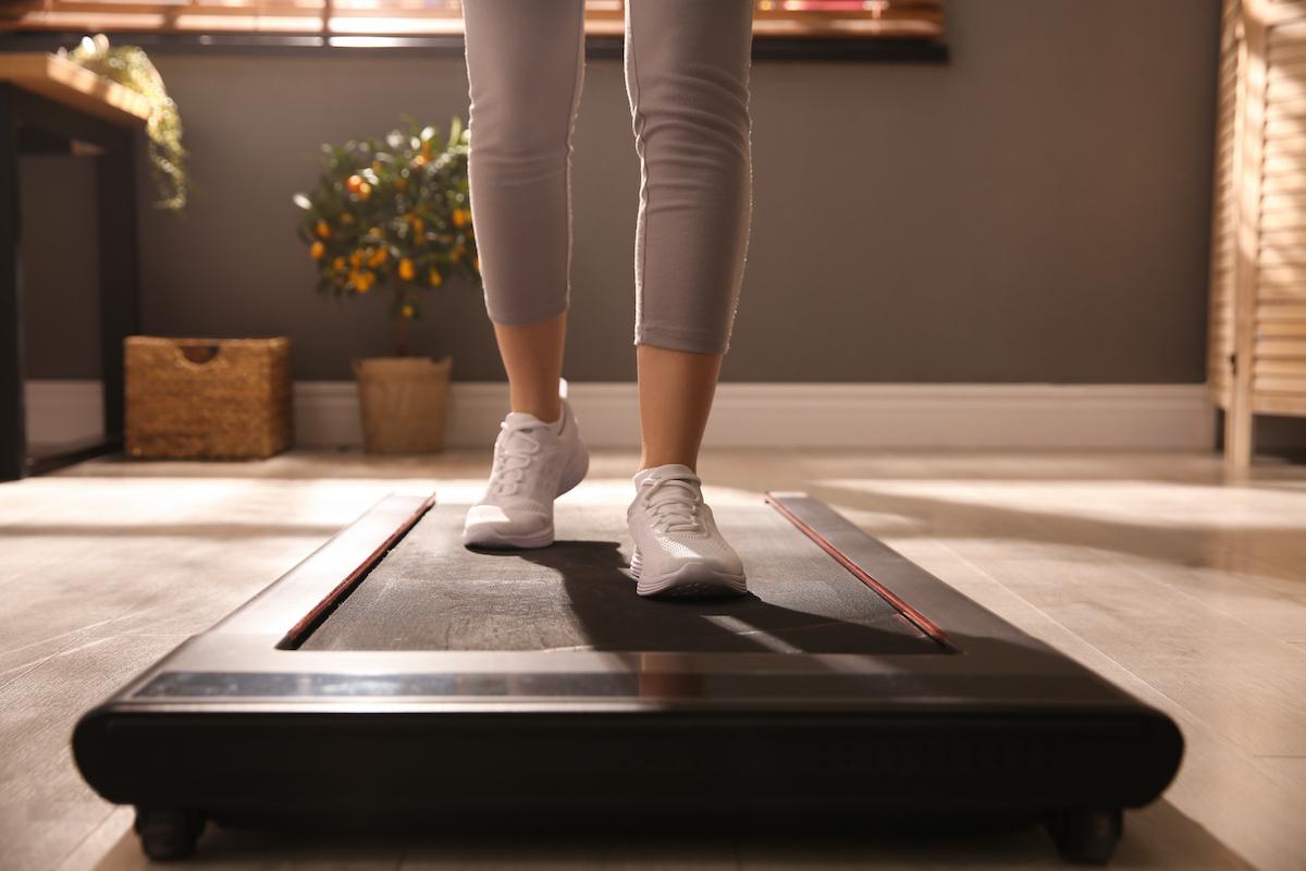 Sporty woman training on walking treadmill at home, closeup