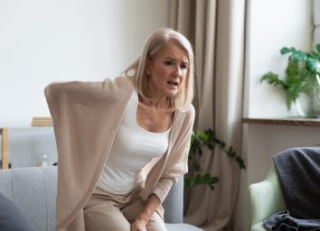 Middle aged mature woman feel hurt sudden back ache touch sore spine at home alone.