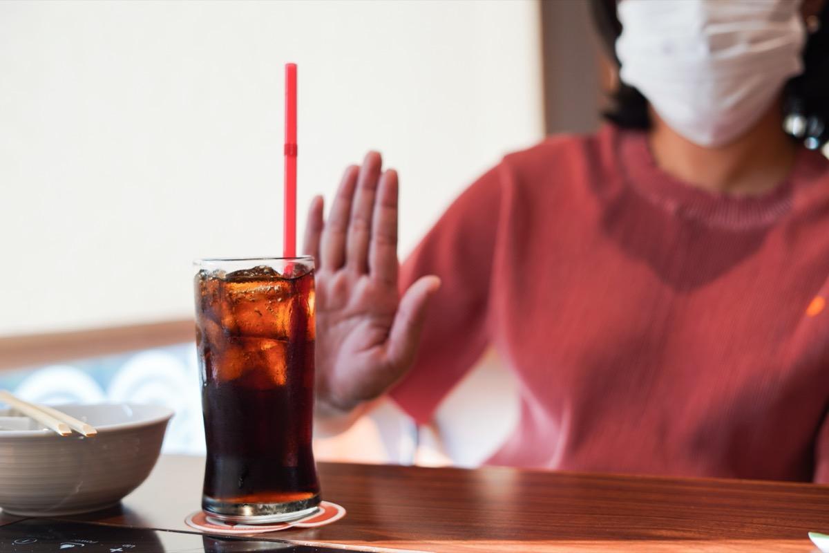 woman wearing mask refusing a glass of soda