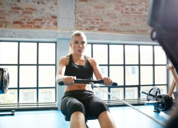 female using rowing machine in the gym. Young woman doing cardio workout in fitness club.