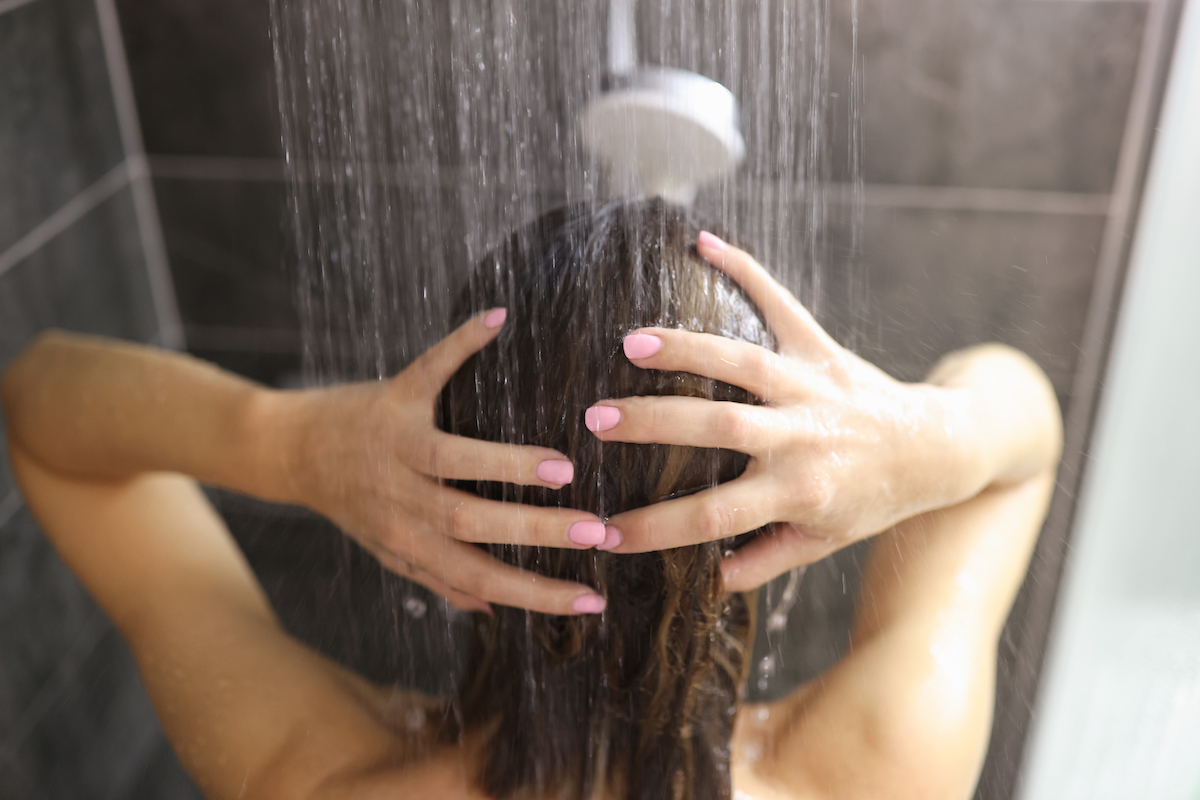 Woman takes shower in the bathroom. Feminine hygiene rules concept