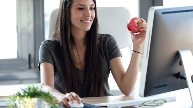 woman sitting at desk eating apple