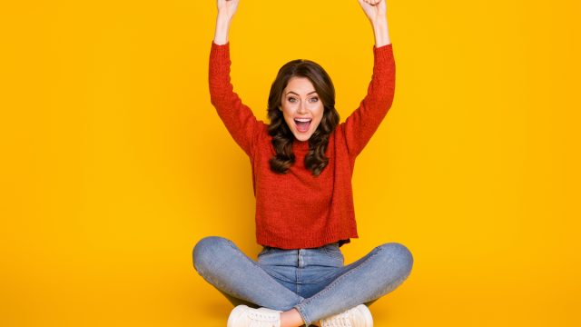 Full size photo of excited energetic girl sit floor legs crossed celebrate lottery win raise fists scream wear jeans jumper isolated bright shine color background