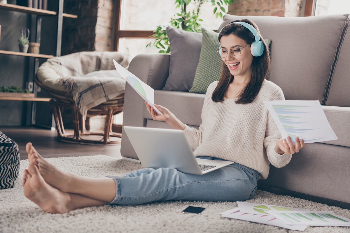 Full body photo of happy pretty girl hold paperwork look computer remote work sit floor inside home indoors