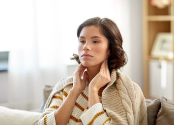 Sick woman touching her lymph nodes at home.