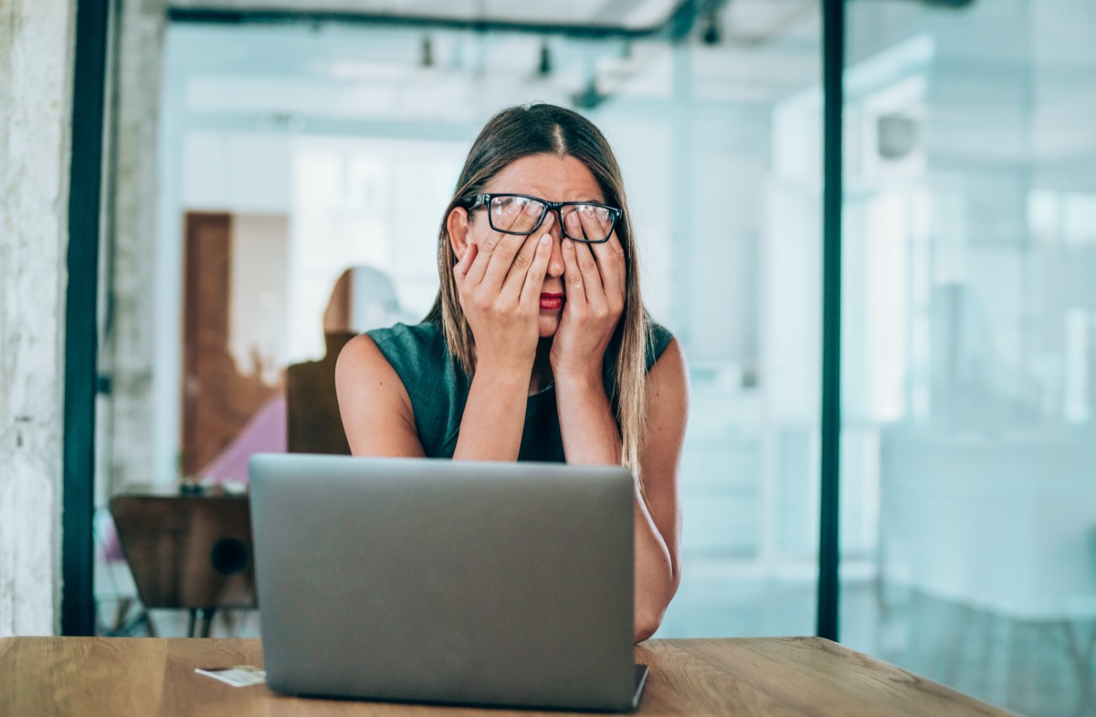 Stressed businesswoman rubbing her eyes in the office.