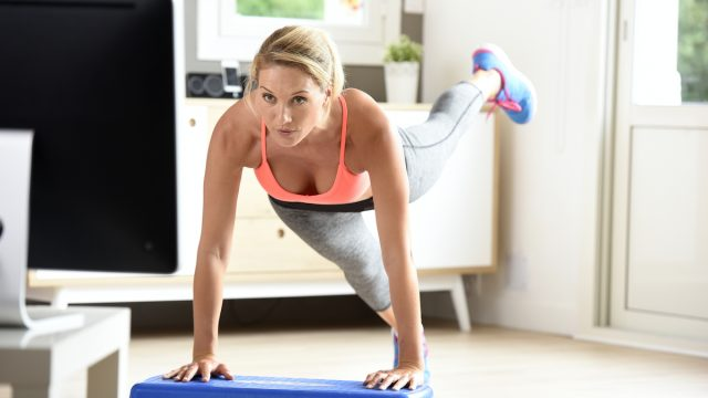 Fitness girl doing exercises in front of TV