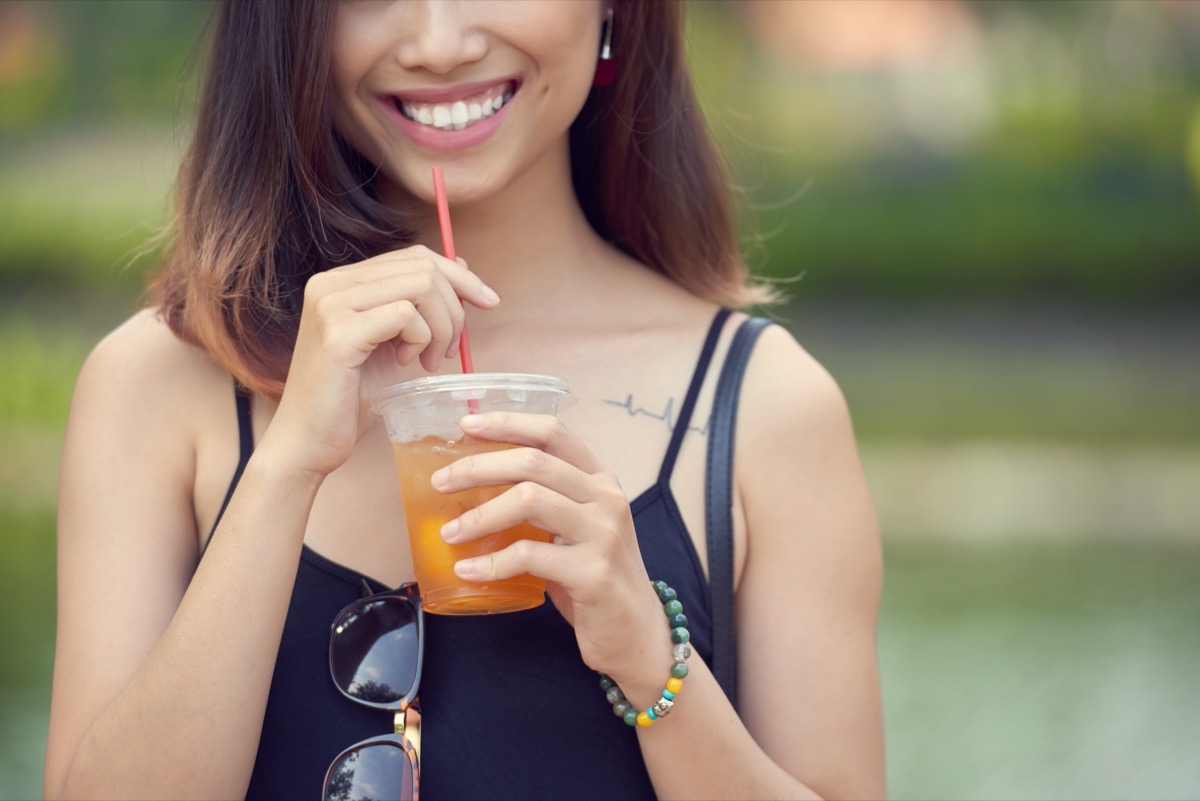 young woman drinking iced tea