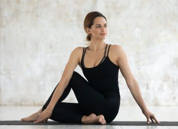 Young woman wear black active wear sit on mat against grunge studio wall background do Ardha Matsyendrasana Half Lord of the Fishes Pose or Half Spinal Twist Pose Vakrasana hatha yoga practice concept
