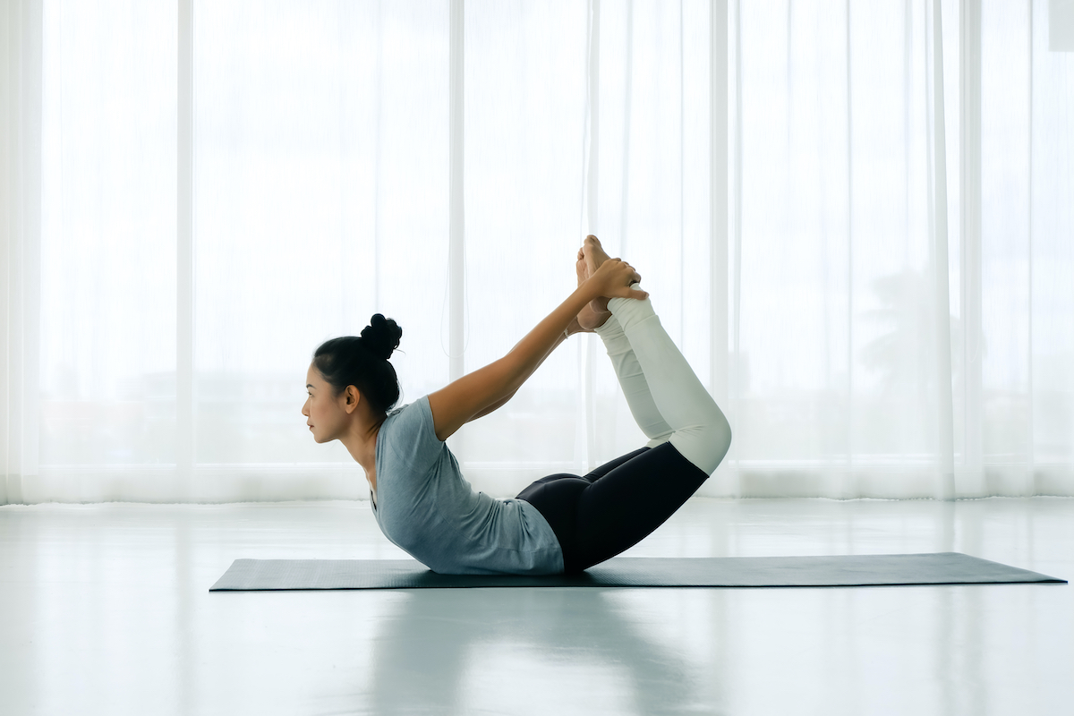Side view portrait of Beautiful Asian woman working out in fitness club or at home, doing yoga or pilates exercise. Dhanurasana, Bow pose,Full length, Concept of healing body and spirit