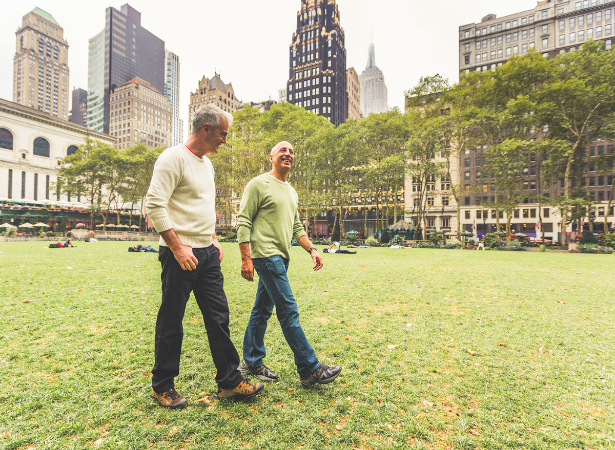 two men walking together in an urban park with buildings behind them