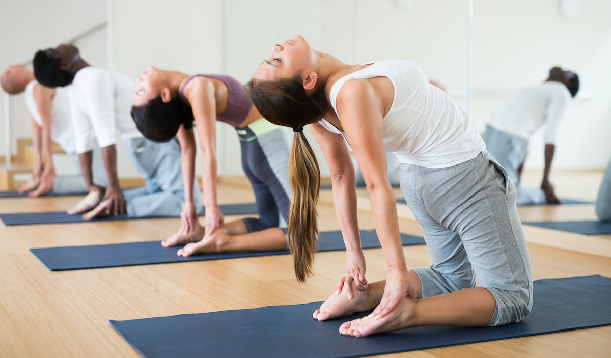 Young concentrated woman performing kneeling back-bending asana Ustrasana (Camel Pose) during group yoga course in fitness studio