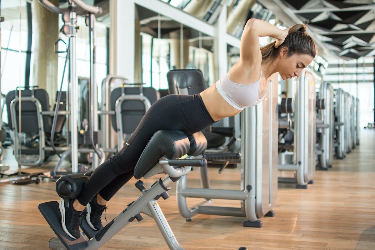 Sports young woman doing exercises on trainer back machine in the gym