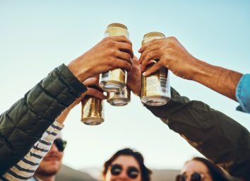 A group of young friends cheersing with beers while enjoying their day out on the beach.