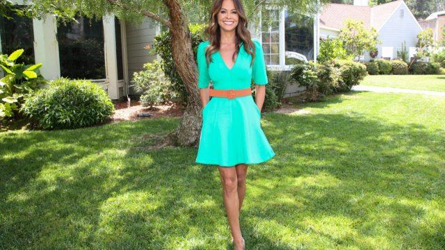 brooke burke in green dress standing outdoors