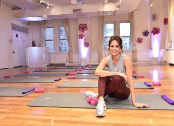 brooke burke sitting on yoga mat in gym