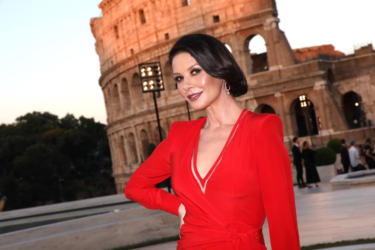 catherine zeta jones posing outside the coliseum in red dress