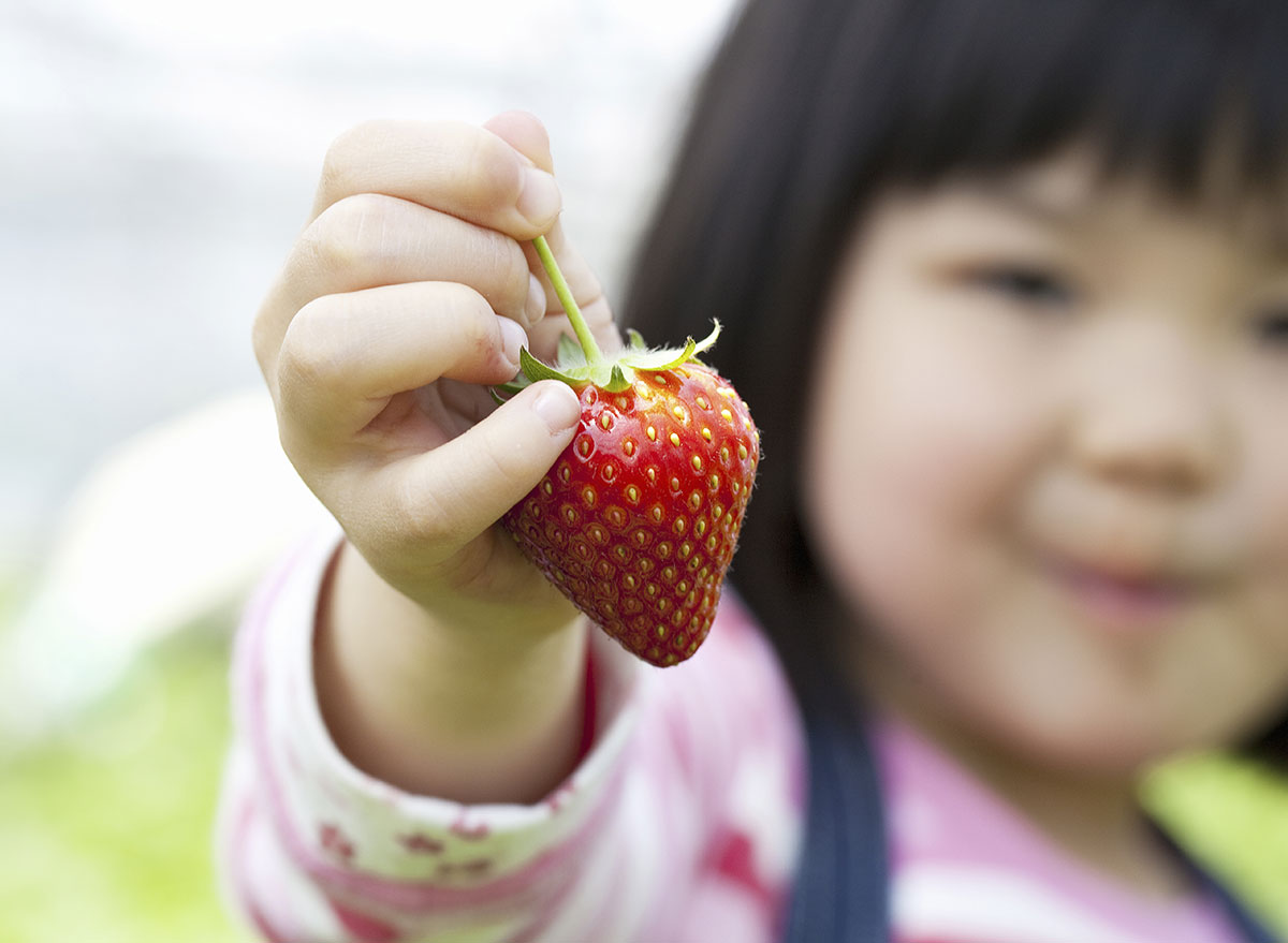 child holding strawberry