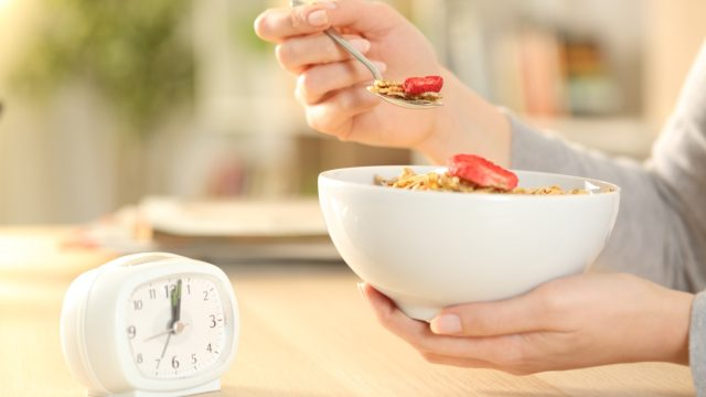 woman eating cereal in front of clock
