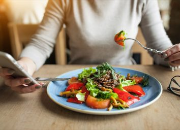woman eating salad and tracking calories on cell phone