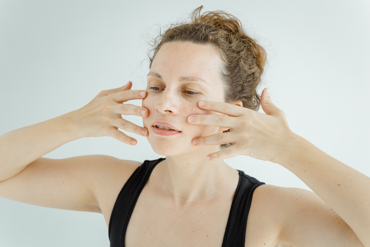 Gymnastics for the face. Cute white woman in black sleeveless sports shirt performing facial yoga. The concept of non-surgical rejuvenation and self-care.