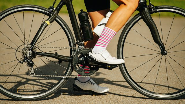 Legs of a female cyclist sitting on a pro slim bike. Cropped, no head. She's wearing striped white and pink socks and low top sneakers with velcro straps.