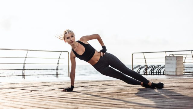 Healthy woman training on seaside promenade. Young sport woman in sportswear doing side plank exercise on the beach at sunrise