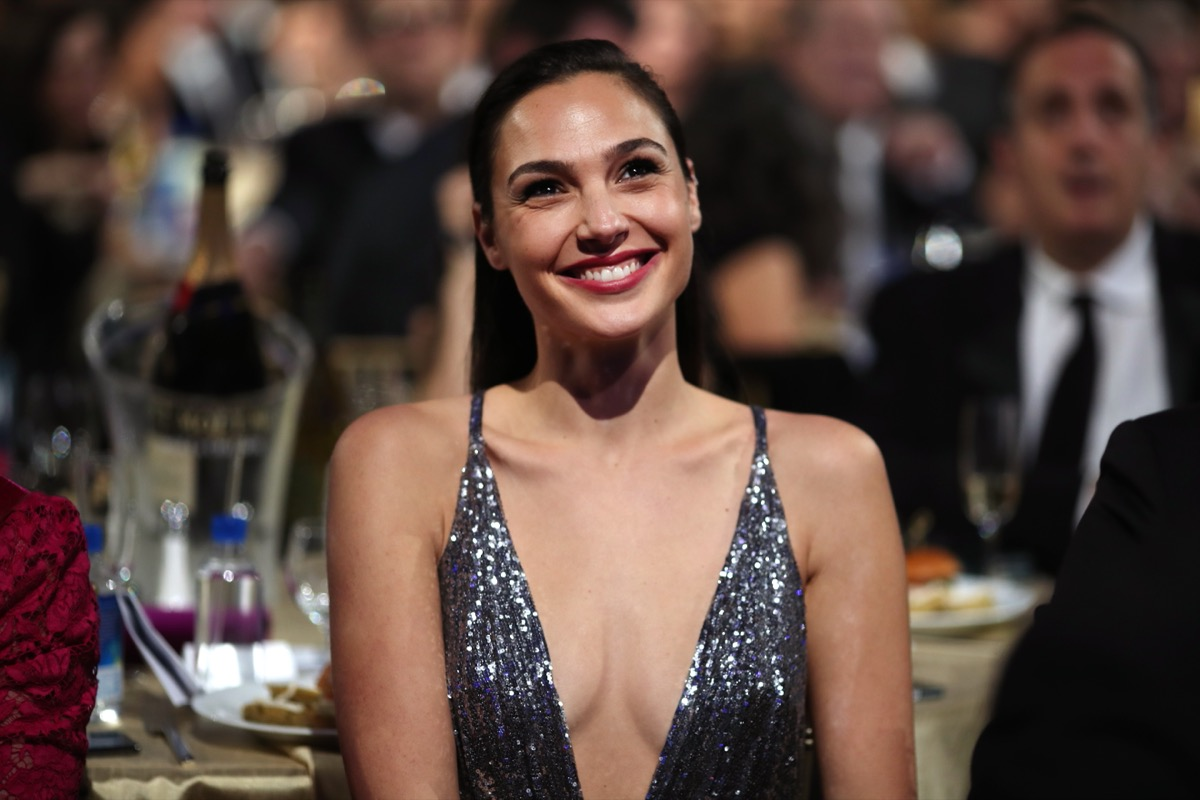 gal gadot in plunging sparkly silver dress smiling while seated
