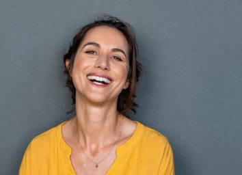 Middle aged woman in casual with toothy smile looking at camera
