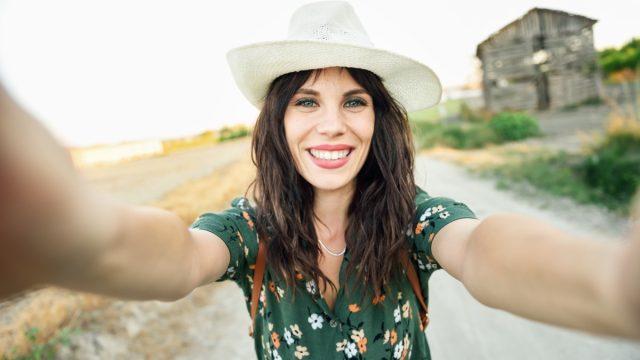 Hiker young woman, wearing flowered shirt, taking a selfie photograph outdoors