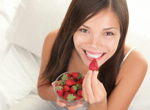 Woman eating strawberries.