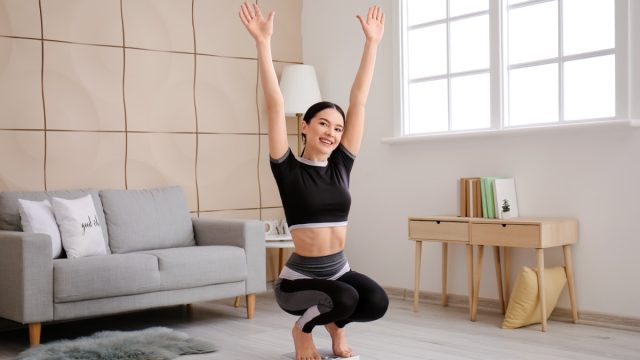 Happy young woman measuring her weight at home