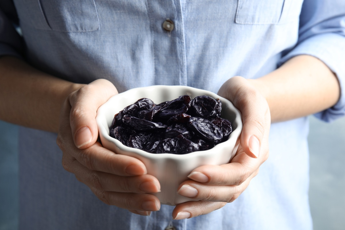 woman holding bowl of prunes
