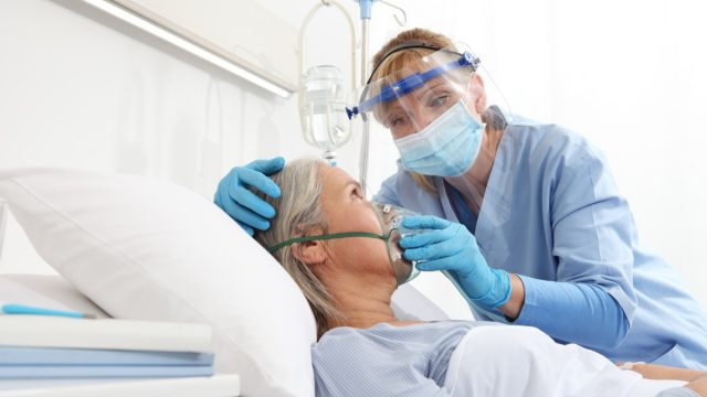 A nurse puts oxygen mask on elderly woman patient lying in the hospital room bed.