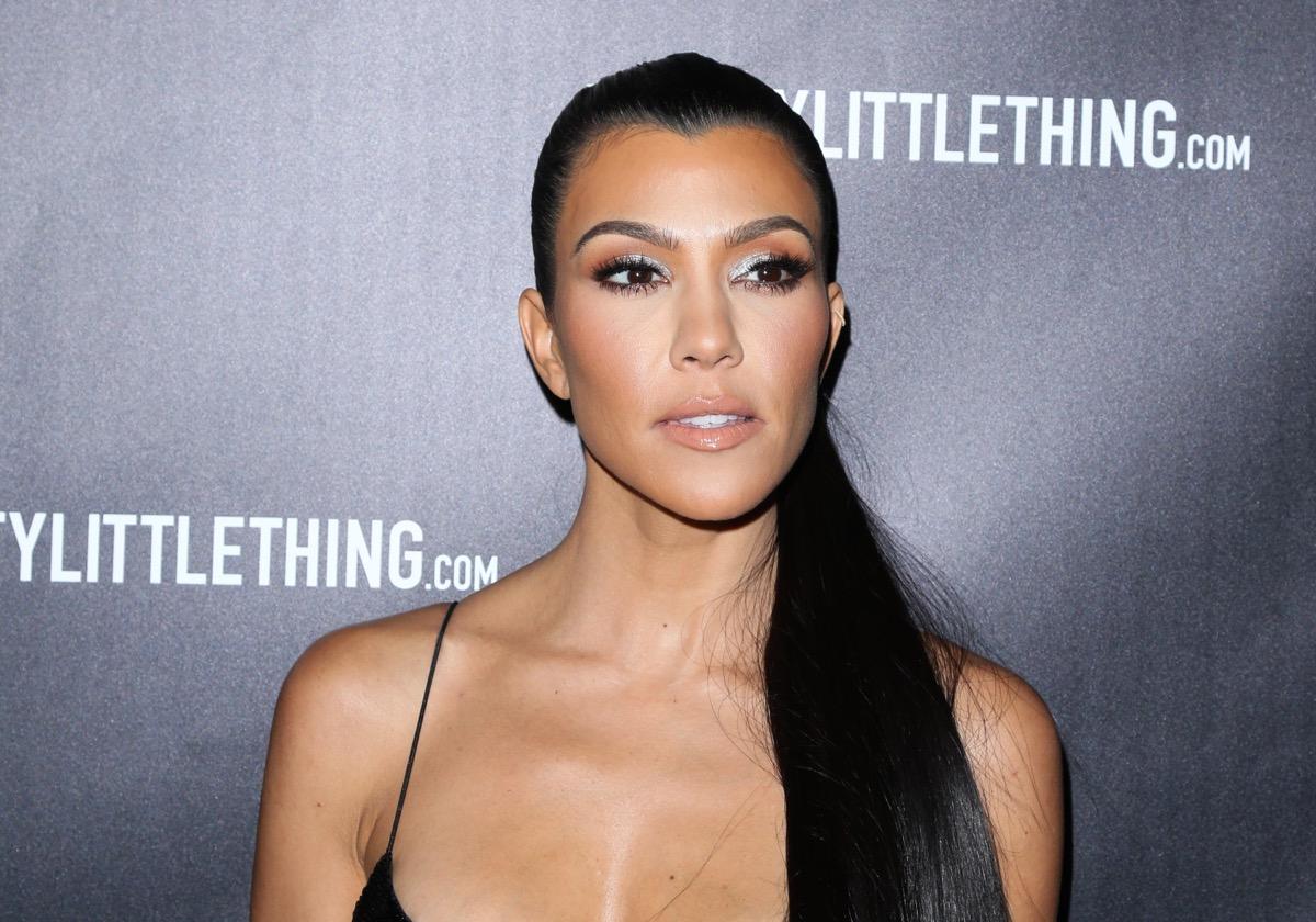 kourtney kardashian on red carpet in black strappy dress