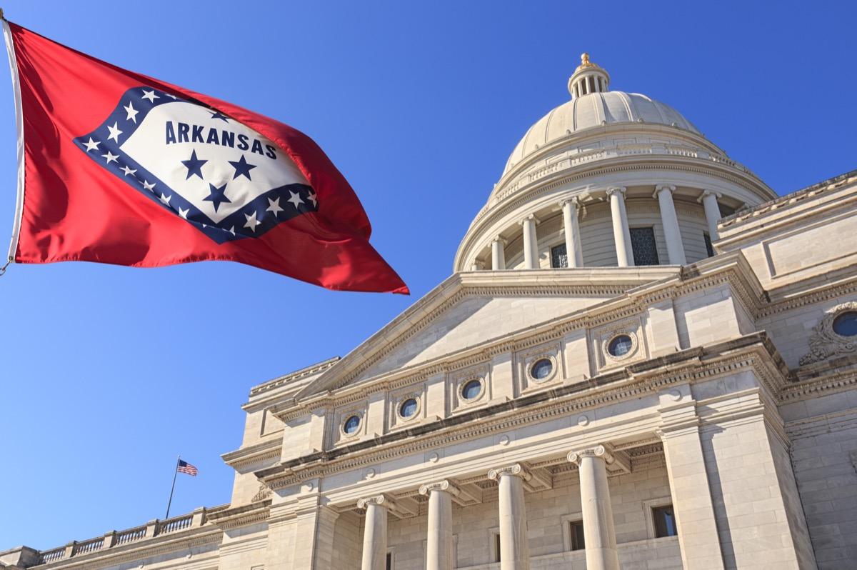 Arkansas flag flying high beside the State Capitol Building