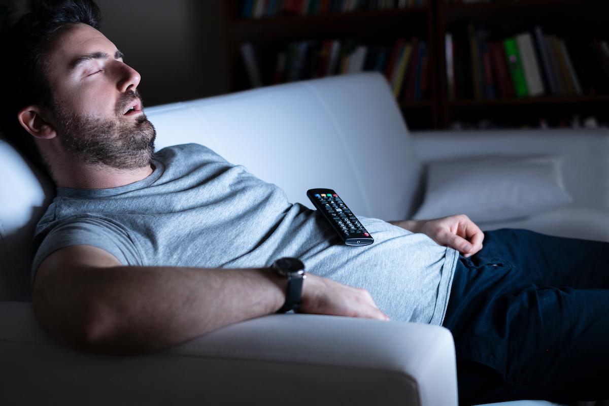 Lazy man watching television at night alone