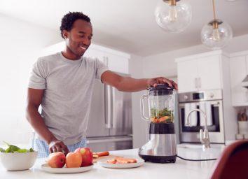 young man making smoothie in modern kitchen