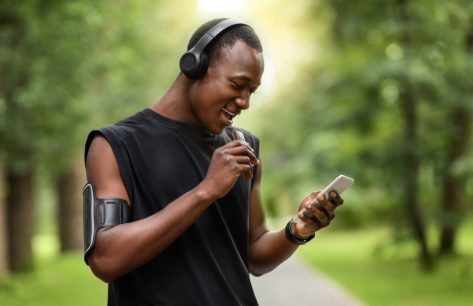 male runner eating protein bar while outside wearing headphones