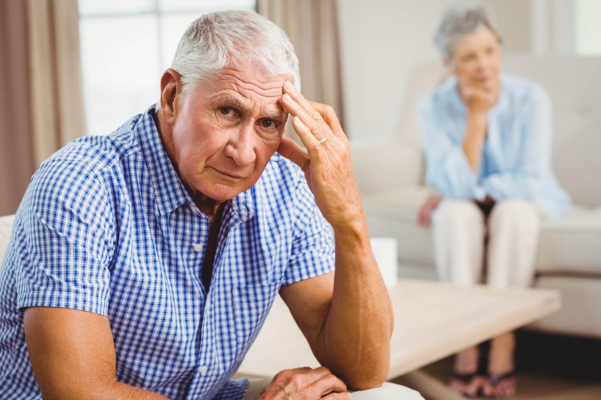 Portrait of worried senior man sitting on sofa in living room