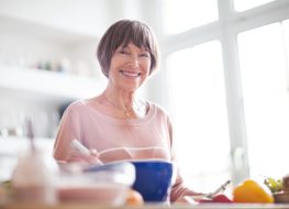 Elderly woman in kitchen looking at camera smiling.