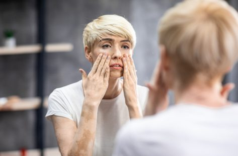 Woman touching face looking at mirror standing in bathroom
