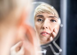Mature woman looking in the mirror touching face standing in bathroom.